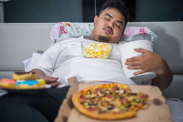 obese man eating a poor diet