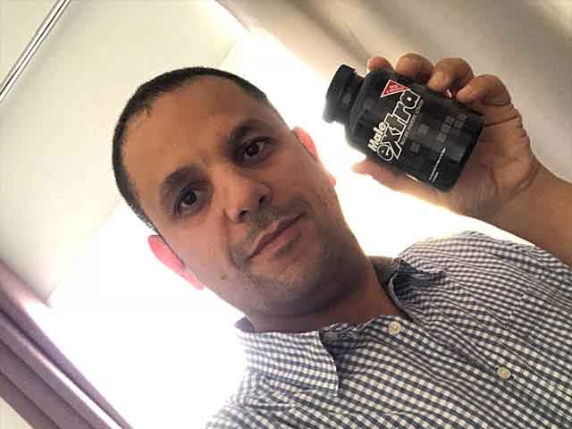 satisfied customer holding a bottle of Male Extra penis pills